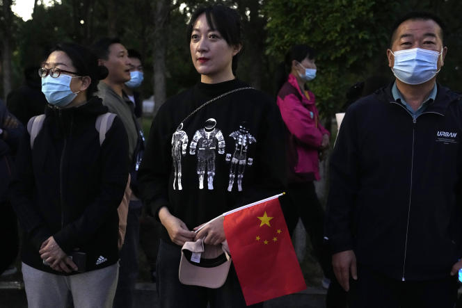 On Thursday, June 17, 2021, an astronaut wearing a space-themed shirt and holding the Chinese flag waits for Chinese astronauts to arrive at the Jiuquan Satellite Launch Center in Juan, northwest China, ready to board the liftoff.  Three astronauts aboard the Shenzhou-12 spacecraft, which will be the first crew members to live in Tianhe or Heavenly Harmony, China's new orbital space station.  (AP Photo / Ng Han Quan)